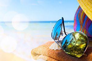 tovallola, barret i ulleres de sol reflexant el palmeres amb el fons del mar