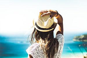 Noia aguantant el barret observant el mar de fons al Taller del Benestar de LLeida