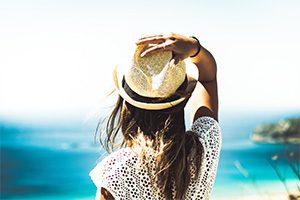 noia amb barret mirant el mar