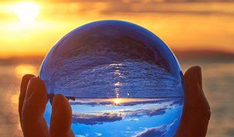 vista de mar amb posta de sol a traves d' una bola de vidre